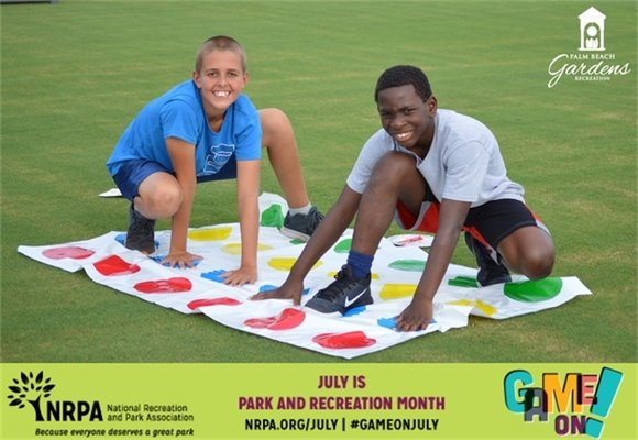 Two boys on a field playing Twister.