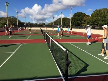 Adults playing pickleball on outdoor pickleball courts.