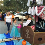 A woman in costume handing candy to a trick-or-treater.
