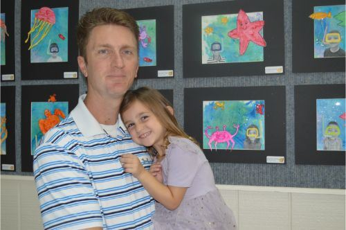 A man holding a young girl and standing in front of art work.