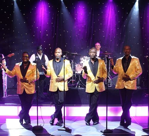 Four men singing with band.