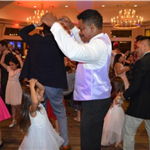 A dad and daughter dancing together in dress clothes.