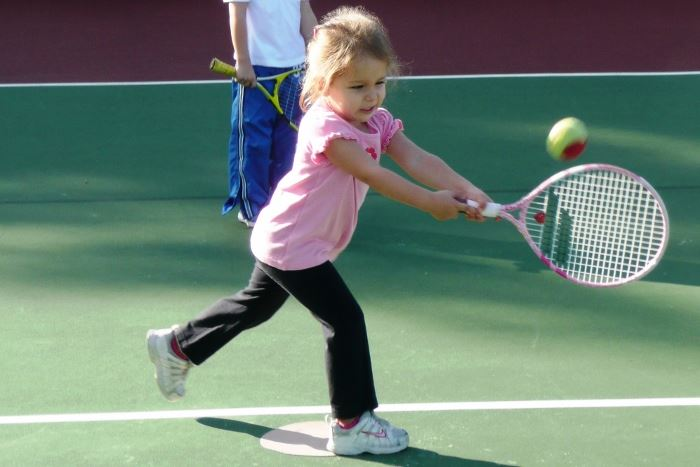 Little girl hitting a tennis ball with a racket