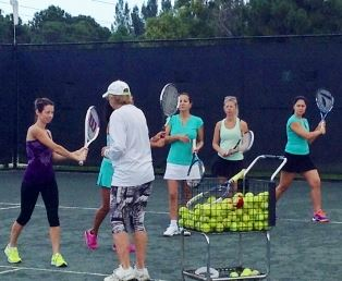 A group of women taking tennis lessons from an instructor
