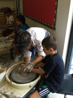 Instructor helping a boy work with clay on the potter&#39s wheel