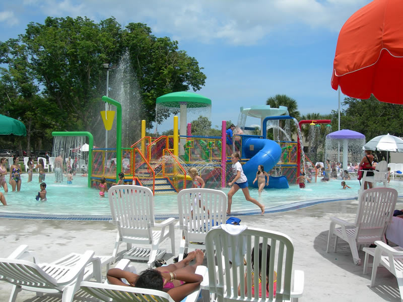 People play in a shallow pool area with slides and other equipment while others lounge in chairs