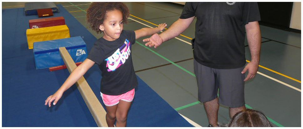A young girl walking on a low Balance Beam
