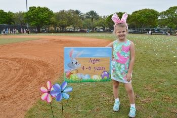 A little girl wearing bunny ears and standing next to an Egg Hunt sign