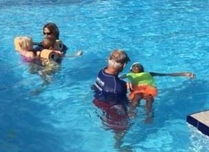 Two instructors teaching swim lessons to two children in Adaptive Aquatics Swim Lessons
