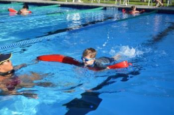 A young boy swimming with the help of a lifeguard.
