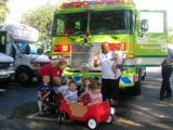 Infant Room kids posing for picture in front of a bright green fire engine