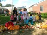 Pre-K Class 2008 kids posing for a picture outside near vegetables dumped out of bins