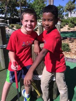 Two young boys playing miniature golf