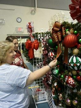 A woman touching a holiday wreath
