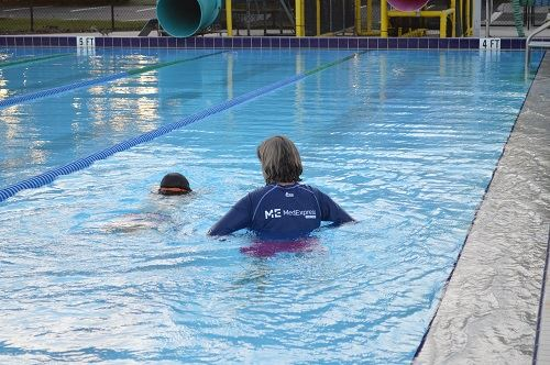 A swimming instructor teaching a child swimming lessons with the MedExpress logo on her shirt