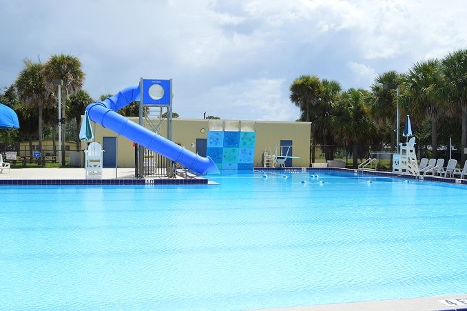 A pool with a slide, rock climbing wall and diving board