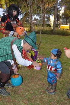 Halloween characters handing candy to a child in costume