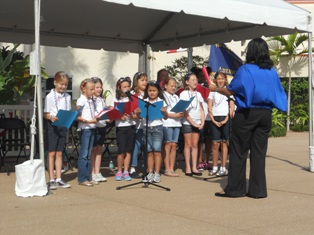 Children singing in a choir directed by a female instructor as part of Sing Out 2013