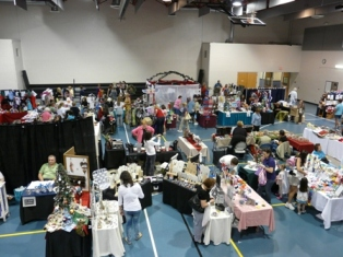 An overhead view of a craft show with booths and people browsing