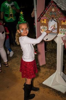 A young girl putting a letter into Santa's Mailbox