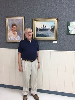 A man standing next to his paintings
