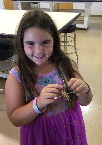 A young girl holding a lizard made from wire and beads