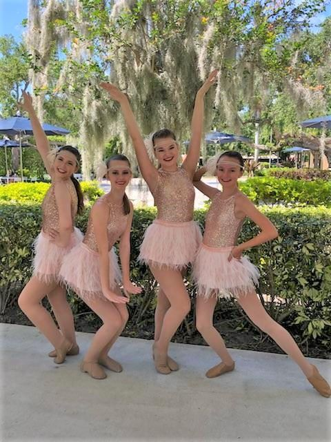 Four dance girls posing in costumes