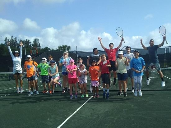 A group of kids jumping up on the tennis court in tennis camp.