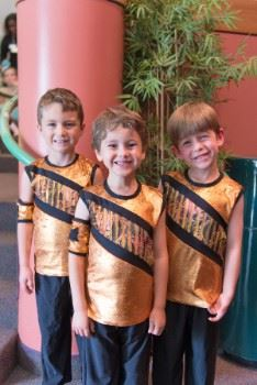 Three young boys in dance costumes