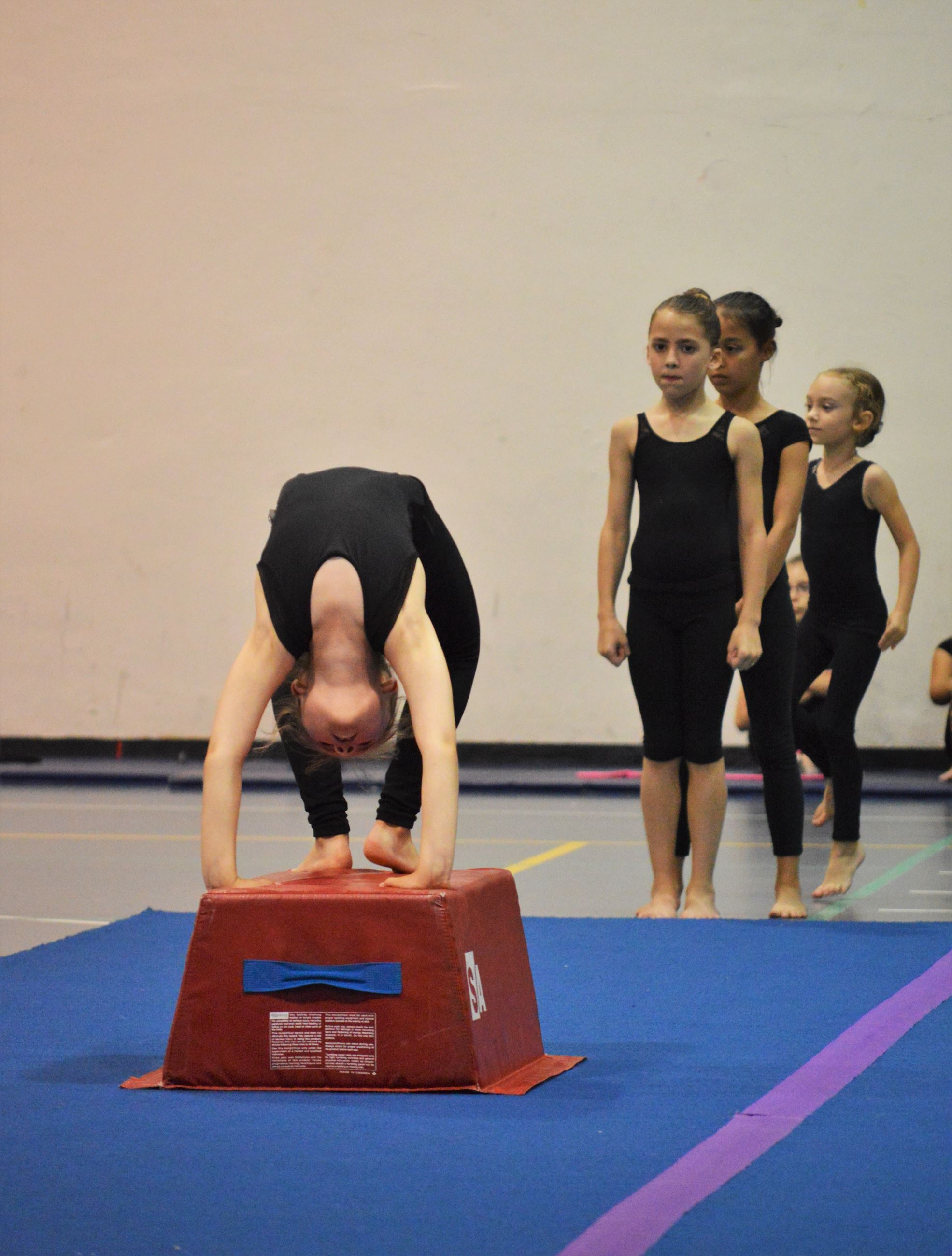 A girl in a gymnastics pose with other girls waiting in line