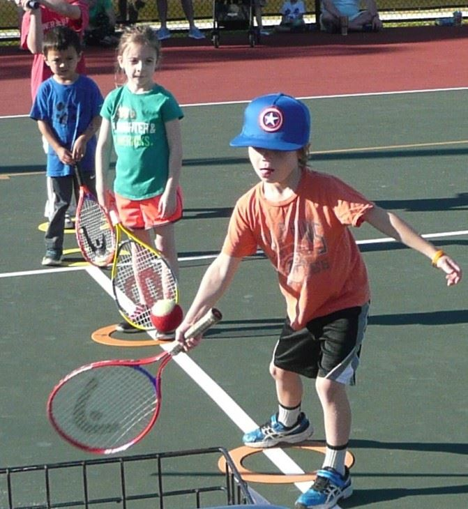 Three young children learning to play tennis.