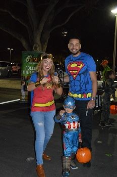 A man, woman and young child dressed in super hero costumes.
