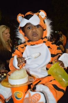 A toddler dressed in a tiger costume eating a slushie.