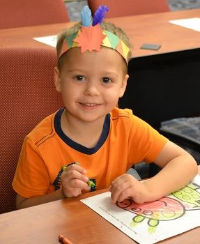 A young boy wearing an Indian headband and coloring a paper