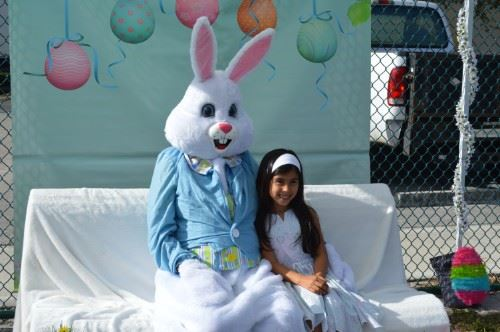 A girl having her picture taken with the Easter bunny