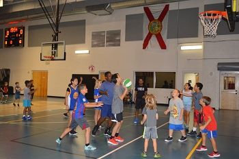 A group of youth playing basketball in the gym.