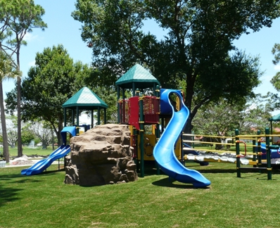 ... PGA Park playground with rock formation for climbing, blue slides and multi-colored equipment