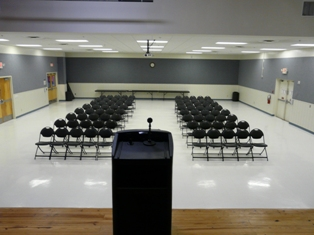 6 round tables with chairs set up for a special event in an indoor facility