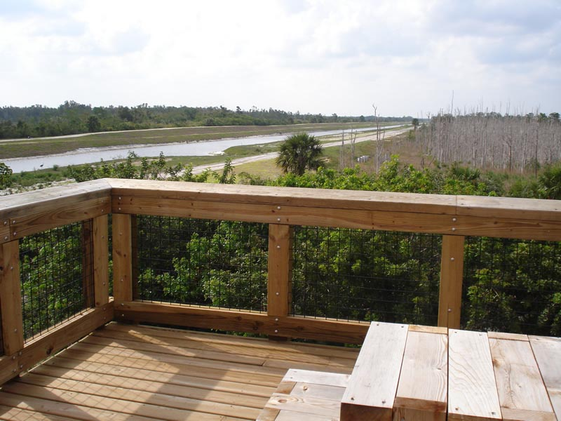 Sand Hill Crane Park view from wooden deck area of canal, a trail and trees