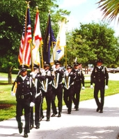 Honor Guard members in dress uniform marching on a sidewalk with ceremonial rifles and flags