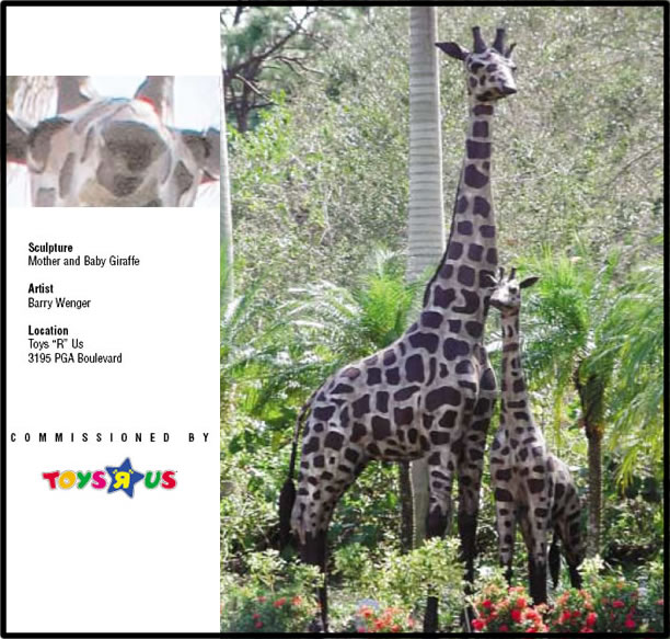 Statues of mother and baby giraffe in wooded area