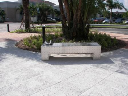 Abstract bench design in paved area under a tree