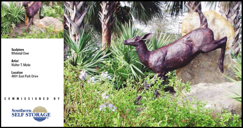 Bronze statue of a whitetail deer in grassy area