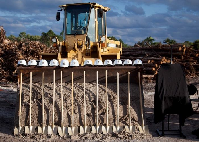 Standing gold shovels with hard hats above them in front of a tractor