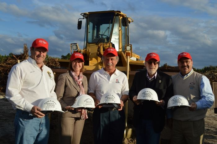 City Council Members wearing caps and holding hard hats in front of a tracto