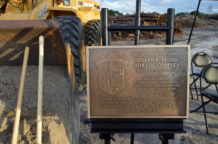 A plaque on an easel next to a tractor with dirt and shovels