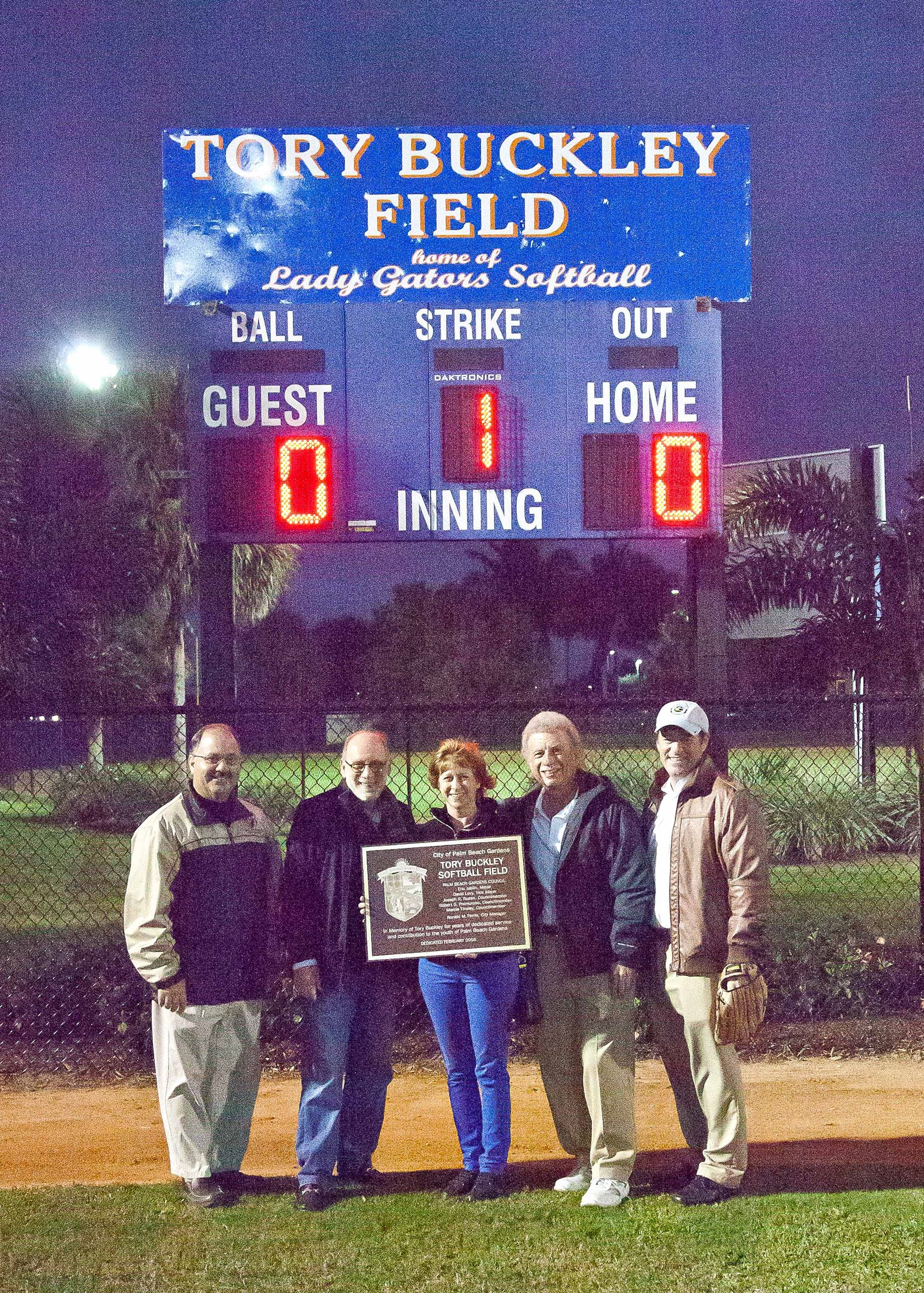 Council Members holding a plaque in front of the Tory Buckley Field scoreboard