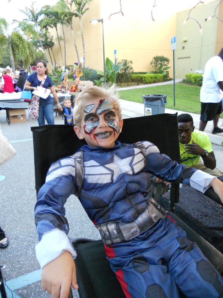 Boy dressed as Captain America sitting in facepainting chair