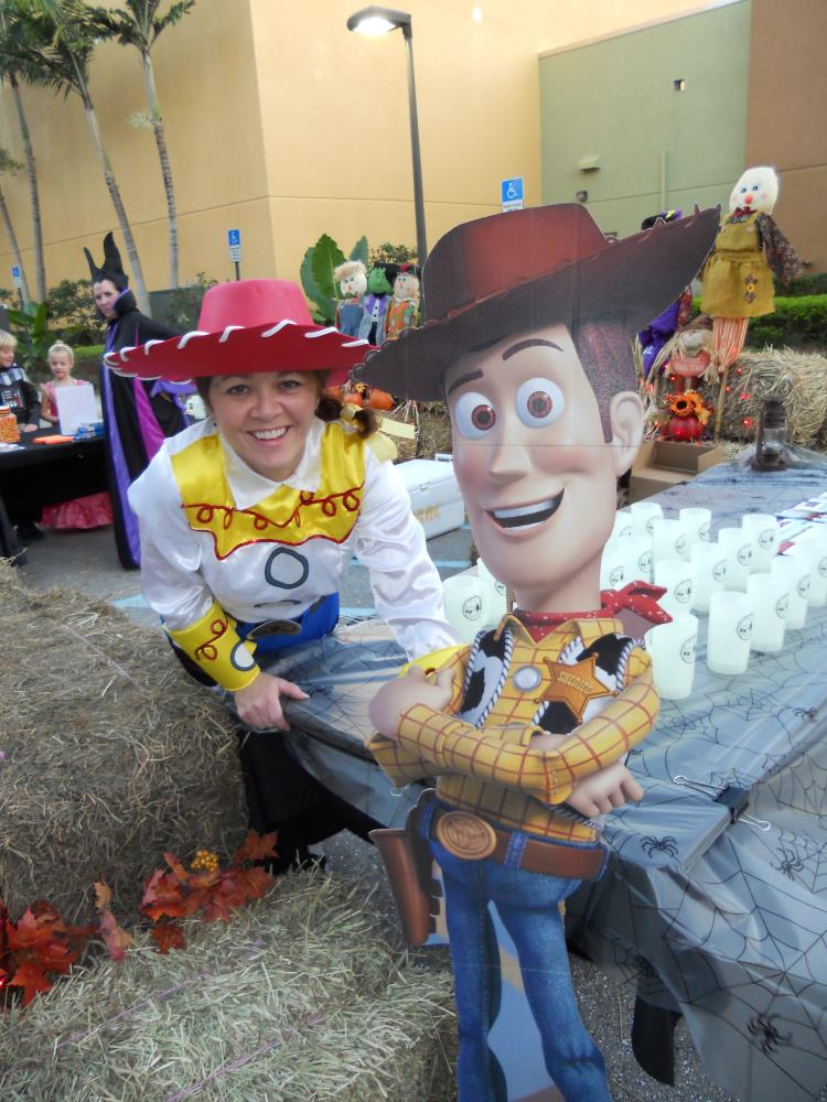 Woman dressed as Jessie from Toy Story takes photo with cardboard cutout of Woody