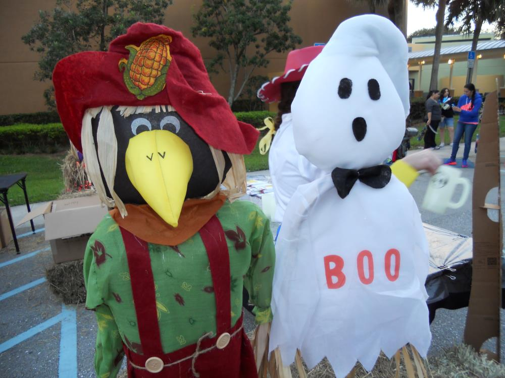 "Crow dressed in scarecrow lawn decoration and white ghost with black bowtie lawn decoration with text ""Boo"" on ghost"